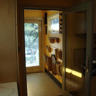 Retro inredning av ett litet kapprum, med gula väggar, linoleumgolv, en enkeldörr och ljus trädörr