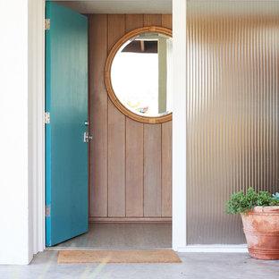 サンタバーバラの中サイズの片開きドアミッドセンチュリースタイルのおしゃれな玄関ドア (白い壁、コンクリートの床、青いドア、グレーの床) の写真