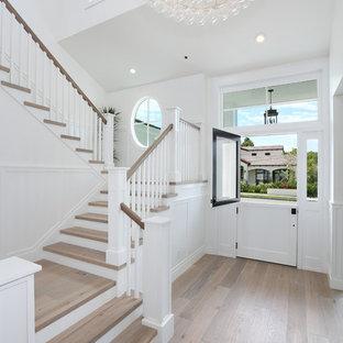 Exempel på en klassisk foajé, med vita väggar, ljust trägolv, en tvådelad stalldörr och en vit dörr
