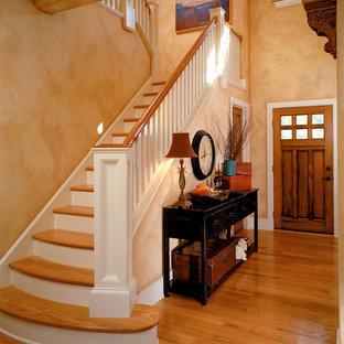 Ejemplo de entrada clásica con parades naranjas, puerta simple y puerta de madera en tonos medios