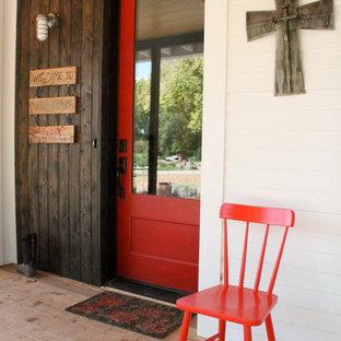 Bild på en mellanstor lantlig ingång och ytterdörr, med en enkeldörr, en röd dörr, vita väggar och mellanmörkt trägolv