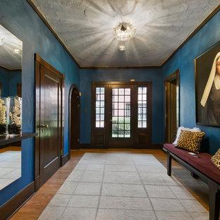 デンバーの片開きドアエクレクティックスタイルのおしゃれな玄関ロビー (青い壁、無垢フローリング、ガラスドア) の写真