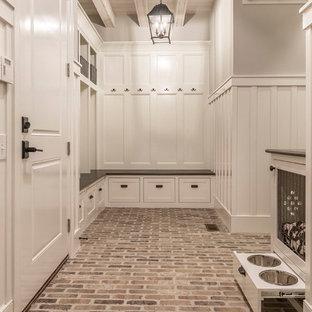 Идея дизайна: большой тамбур в классическом стиле с коричневыми стенами, кирпичным полом, одностворчатой входной дверью и коричневым полом