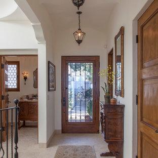 Esempio di un ingresso mediterraneo di medie dimensioni con pareti bianche, pavimento in travertino, una porta singola e una porta in legno bruno