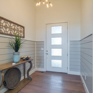 Inspiration for a small transitional medium tone wood floor and brown floor entryway remodel in Boise with white walls and a white front door
