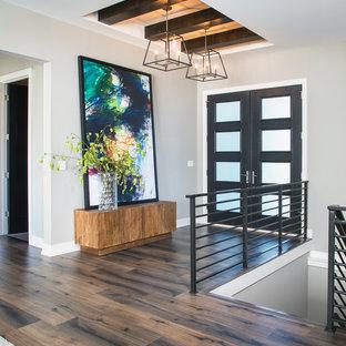 Klassisk inredning av en foajé, med grå väggar, mörkt trägolv, en dubbeldörr, en svart dörr och brunt golv