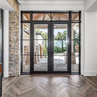 インディアナポリスの巨大な両開きドアカントリー風おしゃれな玄関ロビー (白い壁、淡色無垢フローリング、黒いドア、マルチカラーの床) の写真