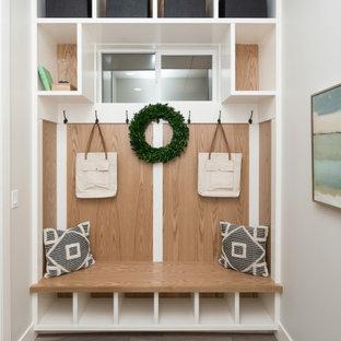 Réalisation d'une entrée champêtre en bois de taille moyenne avec un vestiaire, un mur gris, un sol en bois clair et un sol beige.
