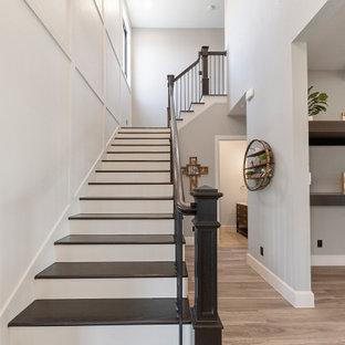 Idées déco pour une porte d'entrée campagne de taille moyenne avec un mur gris, un sol en bois brun, une porte double, une porte noire, un sol multicolore et boiseries.