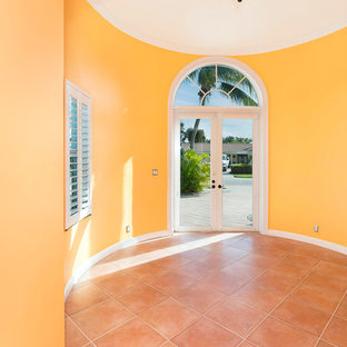 Large coastal terra-cotta floor and pink floor entryway photo in Miami with yellow walls and a white front door
