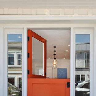 Inredning av en maritim mellanstor ingång och ytterdörr, med vita väggar, betonggolv, en tvådelad stalldörr, en orange dörr och grått golv
