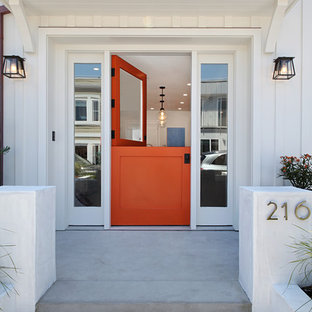 Bild på en mellanstor maritim ingång och ytterdörr, med en tvådelad stalldörr, en orange dörr, vita väggar, betonggolv och grått golv