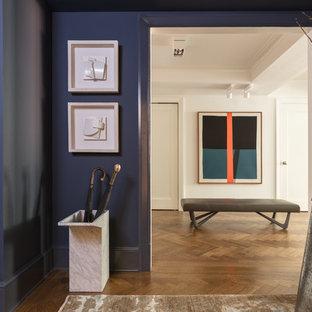 Réalisation d'un vestibule tradition de taille moyenne avec un mur bleu, un sol en bois foncé, une porte simple, une porte métallisée et un sol marron.