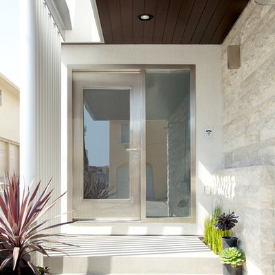 Example of a trendy entryway design in Los Angeles with a glass front door