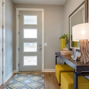 Idee per un corridoio tradizionale con pareti grigie, pavimento in legno massello medio, una porta singola, una porta grigia e pavimento marrone