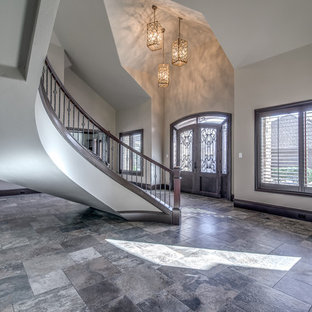 Large tuscan ceramic floor and brown floor entryway photo in Austin with beige walls and a glass front door