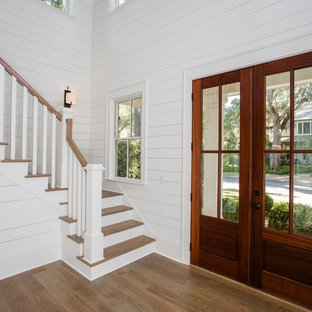 Example of a large country medium tone wood floor and brown floor entryway design in Jacksonville with white walls and a medium wood front door
