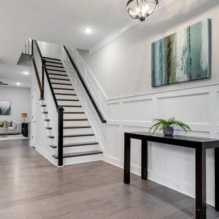 Idée de décoration pour un hall d'entrée tradition de taille moyenne avec un mur gris, un sol en bois brun, une porte simple, une porte en bois brun, un sol marron et boiseries.