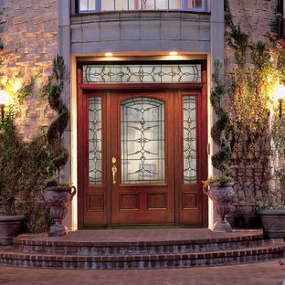 Inspiration for a large timeless brick floor entryway remodel in Tampa with a medium wood front door