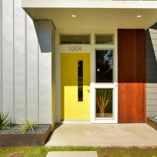 Ispirazione per un ingresso o corridoio contemporaneo con una porta gialla