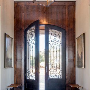 Foto på en stor medelhavsstil ingång och ytterdörr, med vita väggar, kalkstensgolv, en dubbeldörr och mörk trädörr