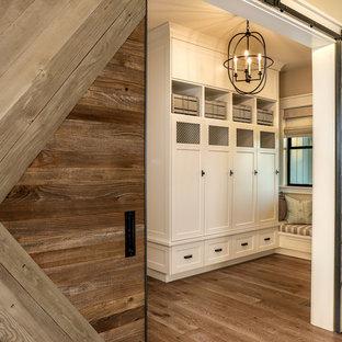 Exemple d'une entrée nature de taille moyenne avec un vestiaire, un mur beige, un sol en bois brun, une porte coulissante, une porte en bois brun et un sol beige.