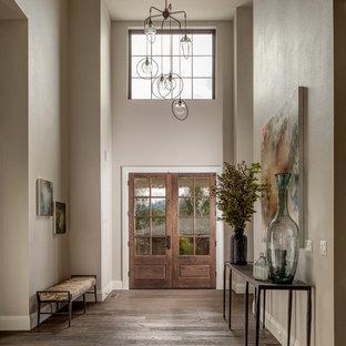 Réalisation d'un grand hall d'entrée champêtre avec un mur multicolore, un sol en bois foncé, une porte double et une porte en bois brun.