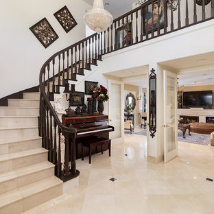 Example of a tuscan beige floor and travertine floor foyer design in Los Angeles with white walls