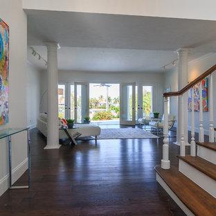 Cette image montre une grande entrée design avec un couloir, un mur blanc et un sol en bois foncé.