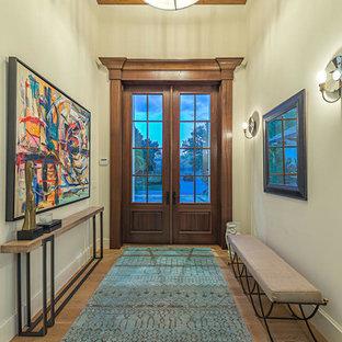 Modelo de entrada tradicional renovada con suelo de madera clara, puerta doble y puerta de madera en tonos medios