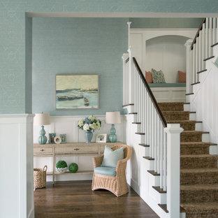Réalisation d'un grand hall d'entrée marin avec un mur bleu, un sol en bois foncé et une porte simple.