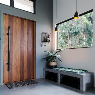 ゴールドコーストの片開きドアコンテンポラリースタイルのおしゃれな玄関ロビー (白い壁、コンクリートの床、木目調のドア、グレーの床) の写真