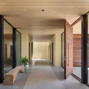 Удачное сочетание для дизайна помещения: узкая прихожая в современном стиле с бежевыми стенами, бетонным полом, серым полом, поворотной входной дверью и входной дверью из дерева среднего тона - самое интересное для вас