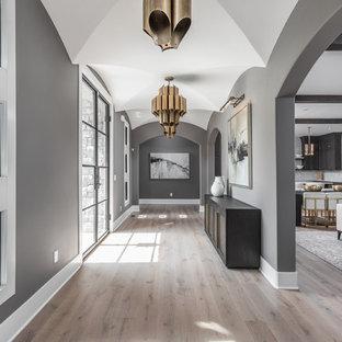 Inspiration pour une très grand entrée méditerranéenne avec un couloir, un mur gris, un sol en bois brun, une porte double et une porte en verre.
