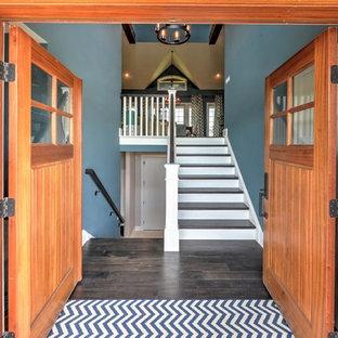 Modelo de puerta principal costera, extra grande, con paredes azules, suelo de madera oscura, puerta doble, puerta de madera en tonos medios y suelo marrón