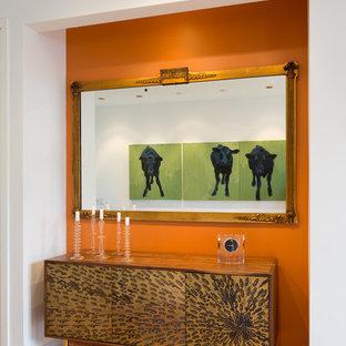 Inspiration för mellanstora moderna foajéer, med orange väggar och ljust trägolv
