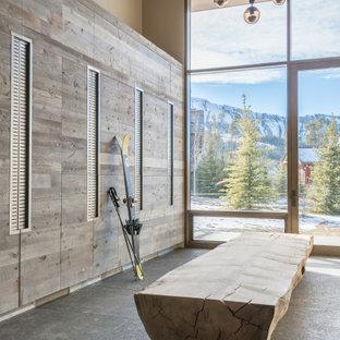 Cette photo montre une entrée montagne avec un vestiaire, une porte simple, une porte en verre, un sol gris et un plafond en bois.