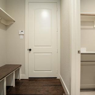 Cette image montre une entrée traditionnelle de taille moyenne avec un vestiaire, un mur beige, un sol en bois brun, une porte en bois brun et un plafond décaissé.