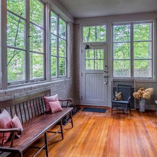 Idées déco pour un grand hall d'entrée classique avec un mur gris, une porte simple, une porte grise, un sol marron et un mur en parement de brique.