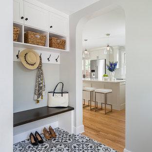 ミネアポリスの中くらいの片開きドアトランジショナルスタイルのおしゃれなマッドルーム (グレーの壁、磁器タイルの床、白いドア、マルチカラーの床、下駄箱) の写真