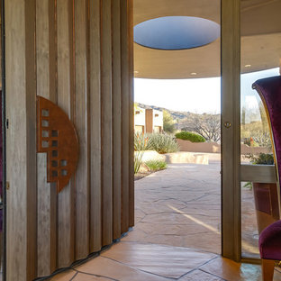 Inspiration pour un très grand hall d'entrée sud-ouest américain avec mur métallisé, une porte pivot et une porte en bois brun.