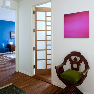 Example of a midcentury modern entry hall design in New York with white walls