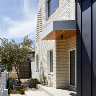 Idee per una porta d'ingresso moderna con pareti bianche, pavimento in cemento, pavimento grigio, soffitto in perlinato, pareti in mattoni e una porta singola