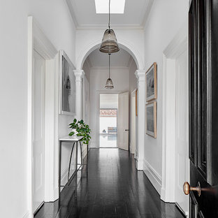 Contemporary entry hall in Melbourne with white walls, black floor, painted wood floors, a single front door and a black front door.