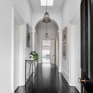 Стильный дизайн: узкая прихожая в современном стиле с белыми стенами, черным полом, деревянным полом, одностворчатой входной дверью и черной входной дверью - последний тренд