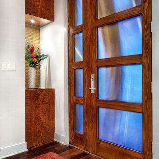 Exempel på en modern entré, med vita väggar, mellanmörkt trägolv och en enkeldörr