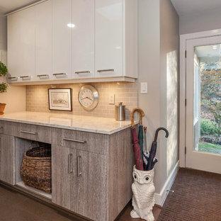 Réalisation d'une grand entrée minimaliste avec un vestiaire, un mur gris, un sol en liège, une porte simple et une porte en verre.
