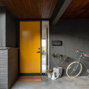Стильный дизайн: входная дверь среднего размера в стиле ретро с серыми стенами, бетонным полом, одностворчатой входной дверью, оранжевой входной дверью и серым полом - последний тренд