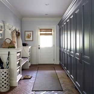 Cette photo montre une entrée chic avec un vestiaire et un sol en brique.