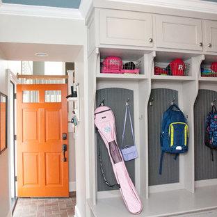Idéer för ett mellanstort klassiskt kapprum, med grå väggar, tegelgolv, en enkeldörr, en orange dörr och brunt golv